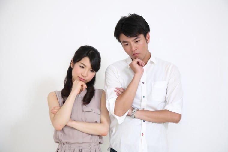 写真:考えごとをするカップル