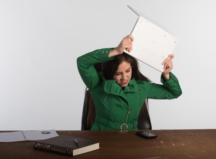 写真:パソコンを投げつけそうな女性