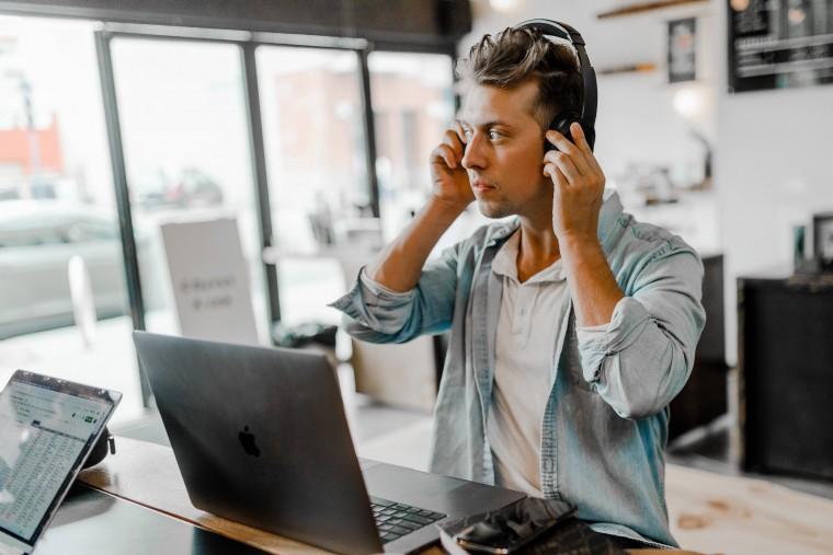 写真:ヘッドフォンをつけてオンラインミーティングをする男性