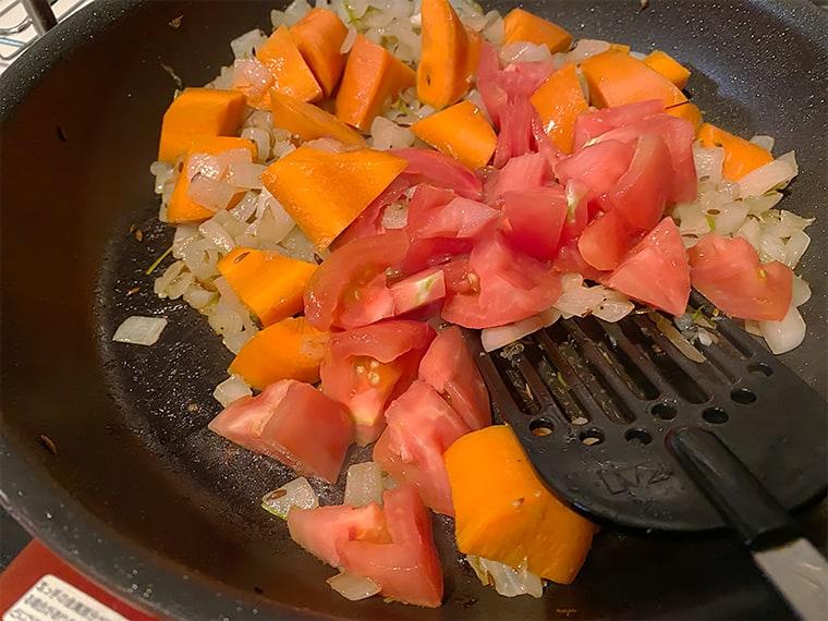 写真:にんじんとトマトを炒める様子