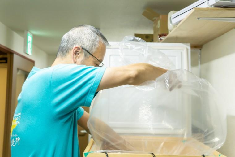 写真:袋を準備する齋藤さん