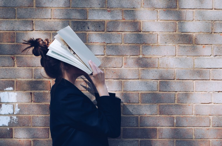 写真:本に頭を埋める人